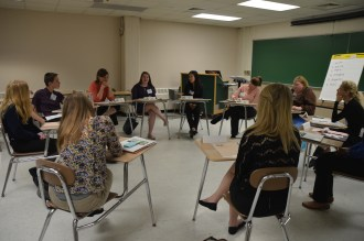 Youth participant, Katie Kurburski, speaks to a group sitting in desks in a circle during the round table session.