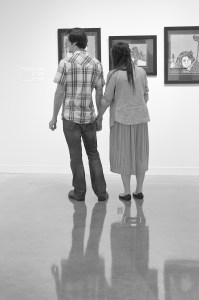 A couple holds hands while viewing New York inspired artwork in the gallery.