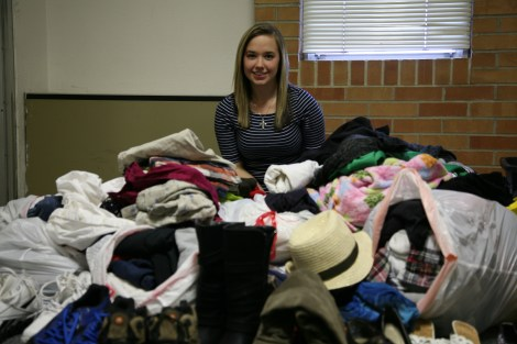 Trish Harwell poses buried in a pile of donated clothing she collects in her Holmquist residence hall room.