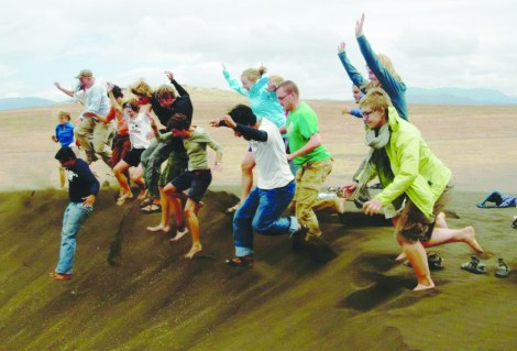 "A past group of MSUM students jump off a sand dune at a place known as ""Shifting Sands"" found in a valley between mountains in north Tanzania. The sand dunes move many inches per year."