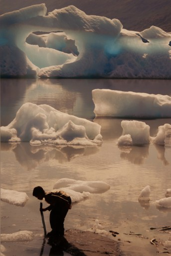 """""""Untitled"""" by Talis Abolins, photograph printed on aluminum. Melting glacier in the background and small child playing in the water in the foreground."""