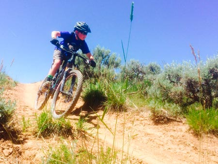 kid shredding trail in the Gunnison Valley