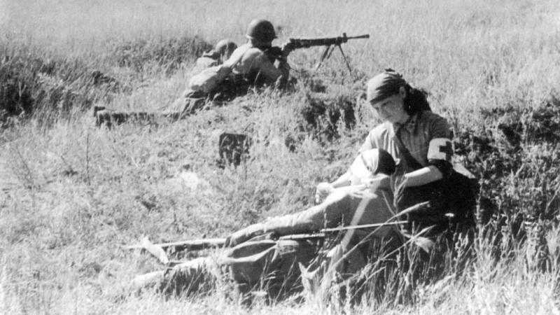 Медсестра В. Смирнова на поле боя оказывает помощь раненому бойцу. 1942. Сталинград, район хутора Вертячий