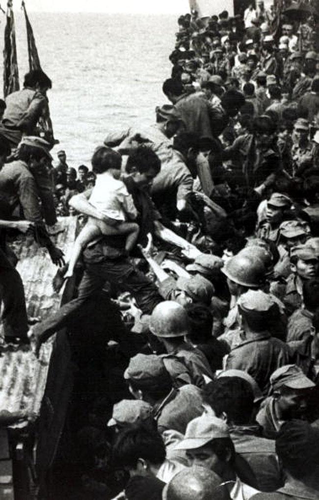 Хюэ, Южный Вьетнам, правительственный солдат, несущий ребенка, прыгает с посадочной лодки на уже переполненный корабль. Март 1975