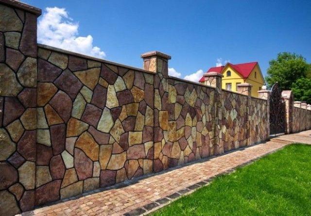 С виду забор из разных цветных камней но нет Это просто на бетоне сделали дизайн дикого разноцветного камня различных размеров