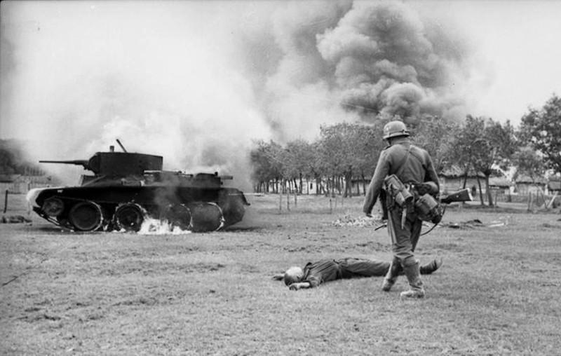 Немецкий солдат и лежащий на земле труп советского солдата у горящего танка БТ-7. 1941г Великая Отечественная Война, история, пропавшие без вести, ссср, факты