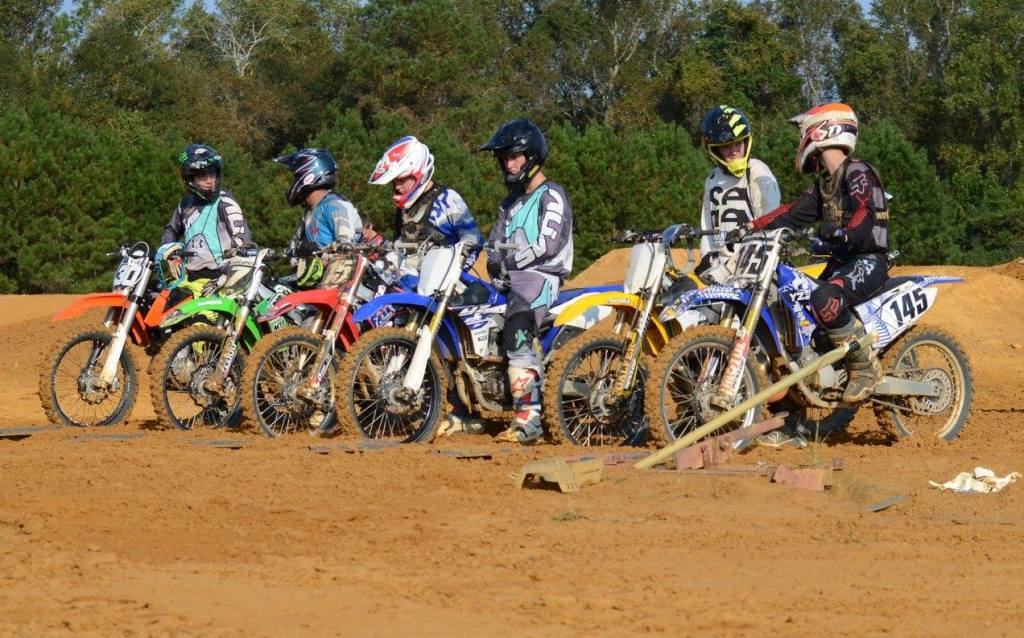 Riders line up at the start gate during practice at the track