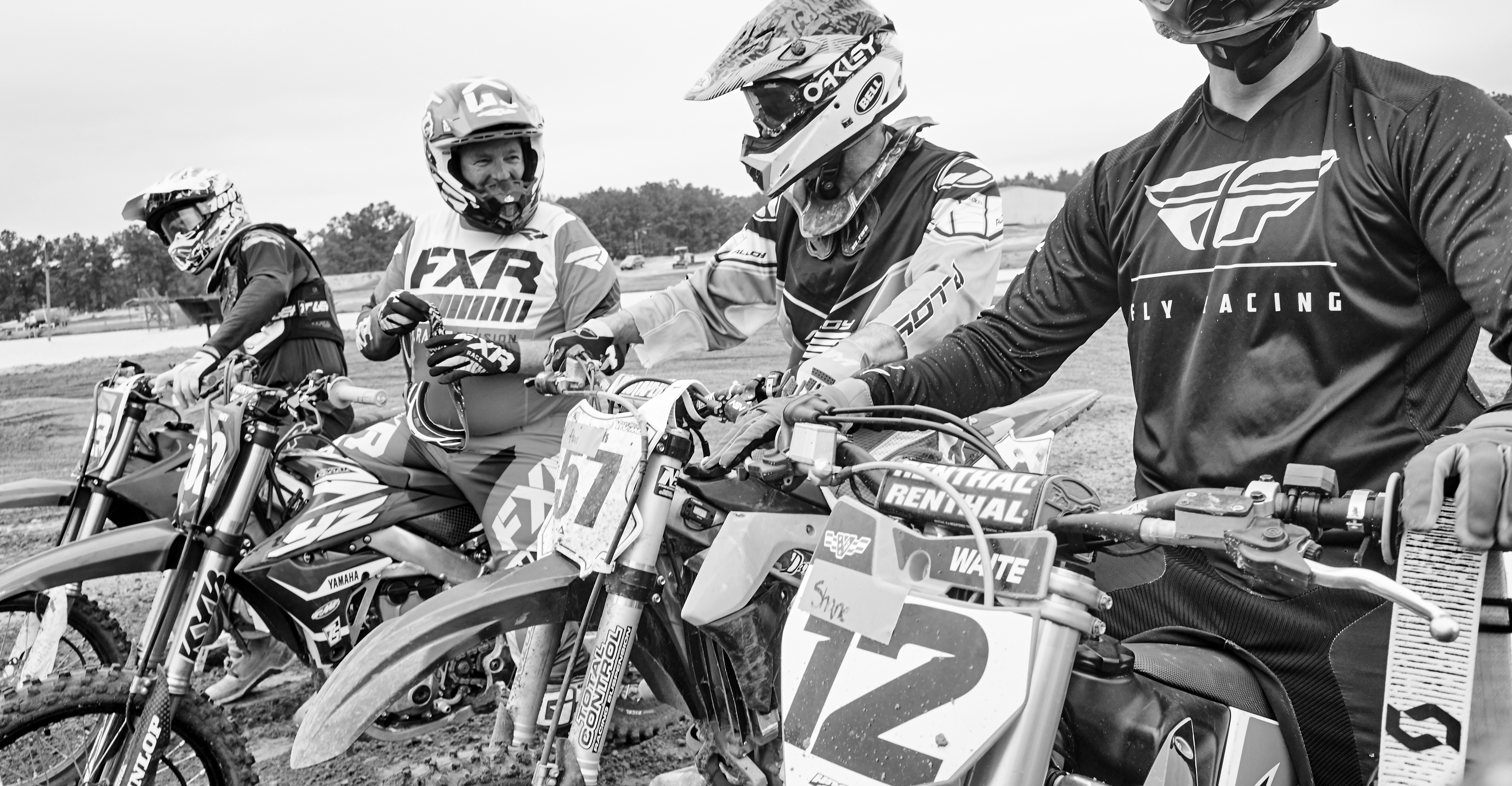 Veterans talk while lining up at the start gate at the supercross track