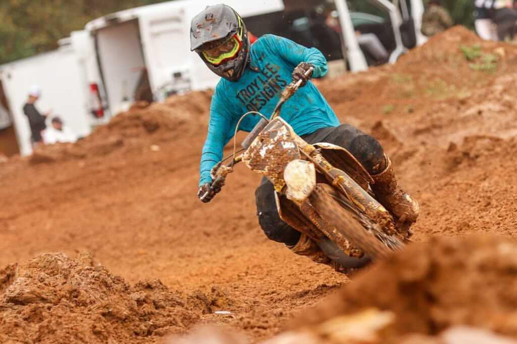 Nicolas Pakciarz races out of a corner on a muddy motocross track.