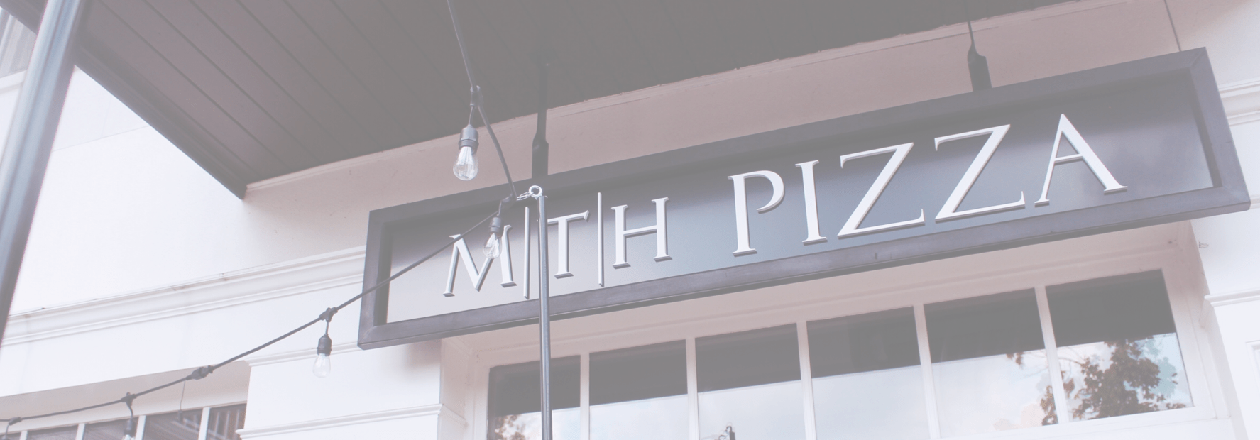 The sign and hanging lights above the dining entrance to MTH Pizza in Smyrna
