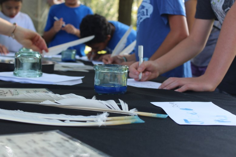 Children practice writing with quill feathers at Oaklands Mansion's Autumn in the Oaks Educational Field Day in Murfreesboro, Tenn. on September 21, 2017. (Shade Narramore / MTSU Sidelines)
