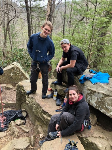 Samantha War celebrates the completion of her most difficult climb to date with two fellow climbers, Nate Valentine (left) and Eric Snoek. They are sitting on a rock face in the woods, surrounded by their climbing gear.