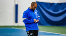 MTSU Men's Tennis coach Jim Boredame stands on a tennis court while writing a note.