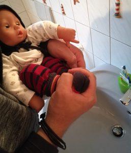 Kleines Baby wird über dem Waschbecken abgehalten