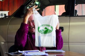 Rockwell shows students other keepsakes from his life, such as this bag from the cheese company Productores de Monteverde S.A. Photo by McGuire McManus