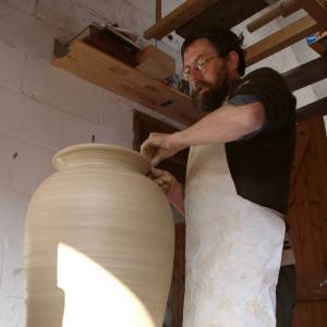 Douglas standing up, throwing a very large pot