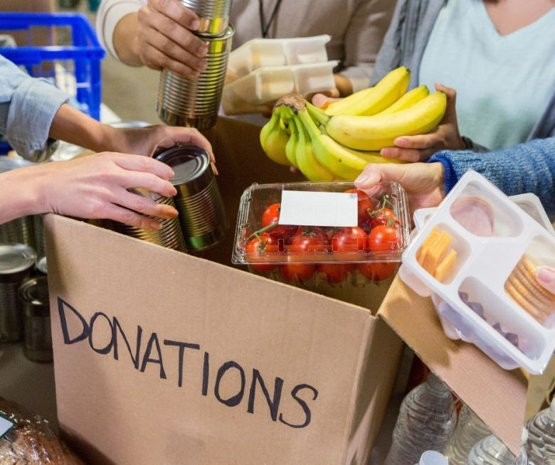 Hands holding food to put in cardboard box marked donations