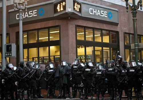 Police in riot gear protecting a bank