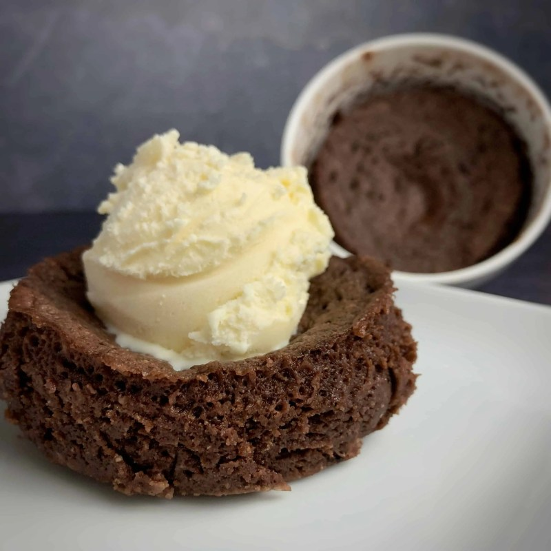 chocolate protein mug cake on a plate and a second mug cake in the mug