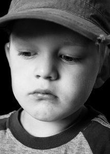 Na obrázku je smutné dítě v kšiltovce
