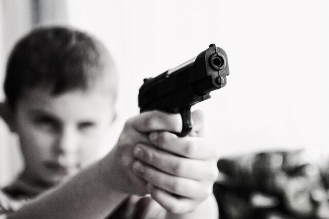 Chlapec na obrázku drží pistoli