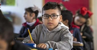 Na obrázku je dítě, které sedí ve třídě a dívá se do kamery, v rukou drží tužku