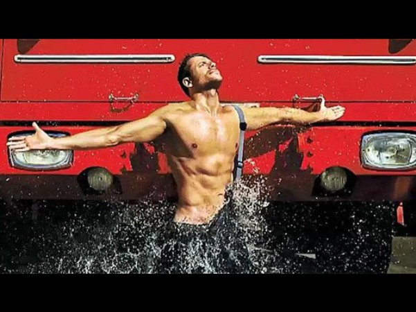 En la foto se ve a un bombero con el torso desnudo mientras le salpica agua. De fondo el morro de un camión de bomberos.