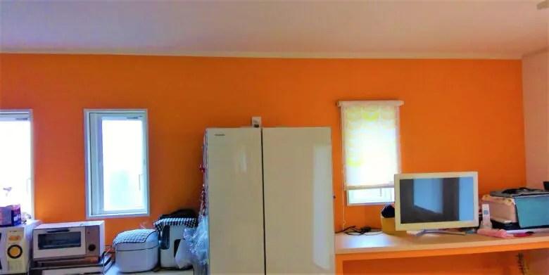 キッチン背面のオレンジ色のアクセントクロスは狙い通り。視覚的効果でしっくりくる