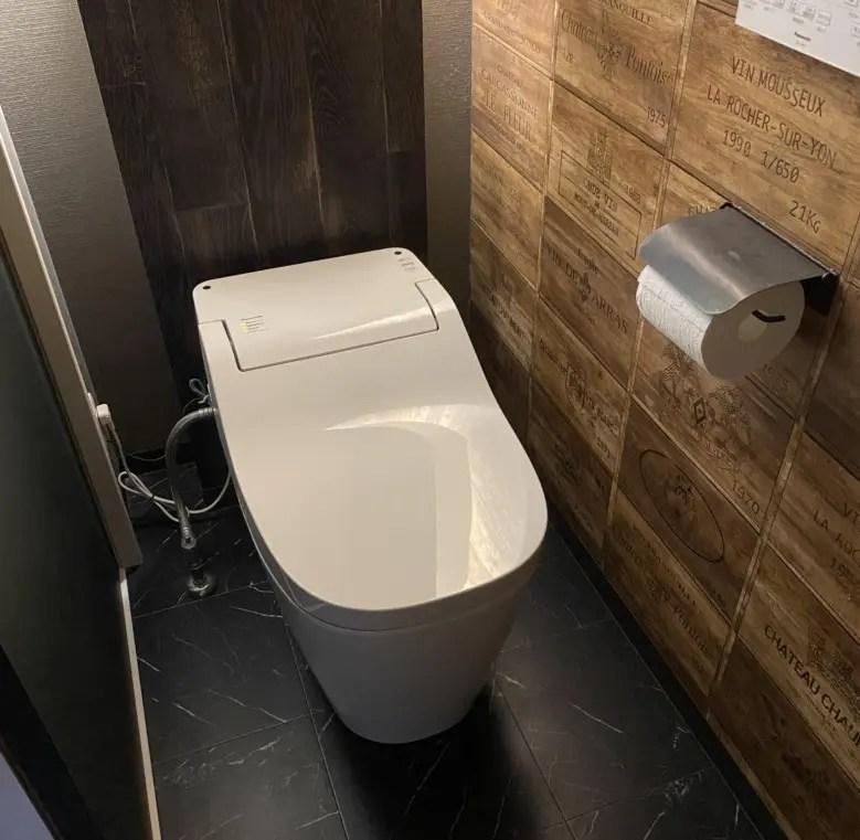 トイレっぽさがない、ヴィンテージ風ワインボックスで狭さを軽減。黒い床でシックにまとめる