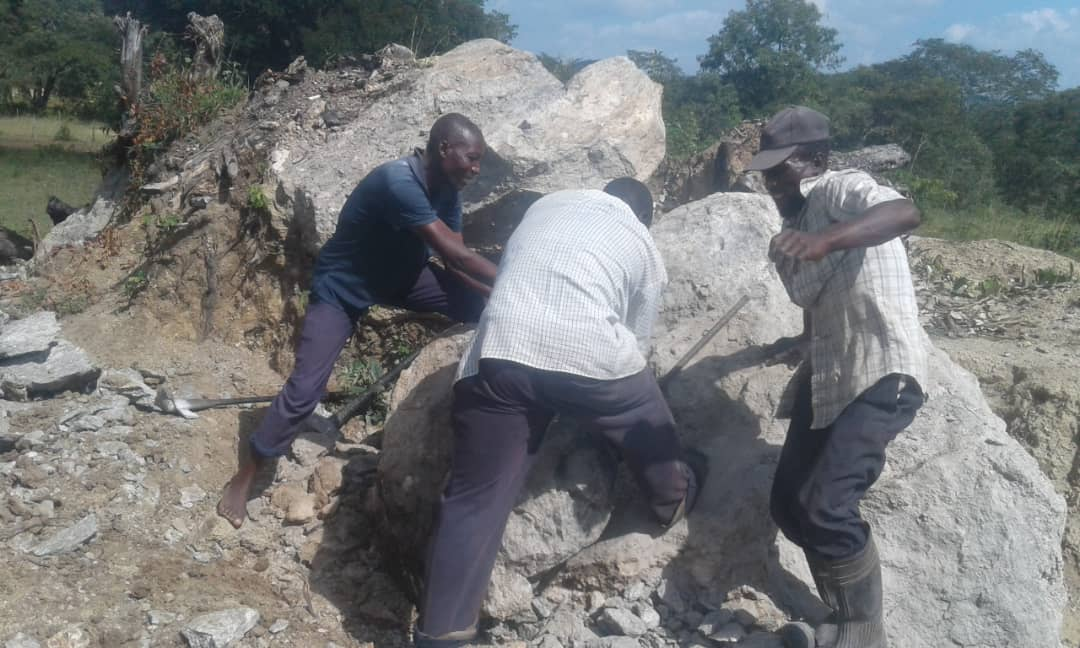 Men at work clearing stones