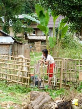 Malgré le froid matinal, la femme lave son linge à Nong Khiaw au Laos