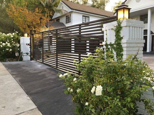 Iron driveway gate with horizontal slats