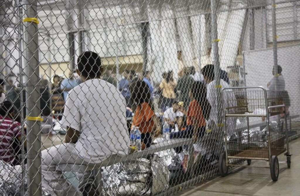 People who were taken into custody, related to cases of illegal entry into the United States, sit in one of the cages at a facility in McAllen, Texas, in June.