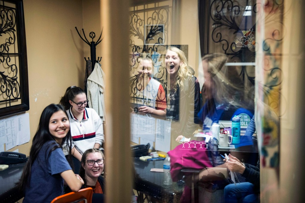 The Temple Academy girls basketball team gathers in the coach's office before practice at Temple Academy in Waterville on Friday. Students from nine countries are on the team. Several have never played basketball, but the team is headed for the state tournament with a 14-4 record.
