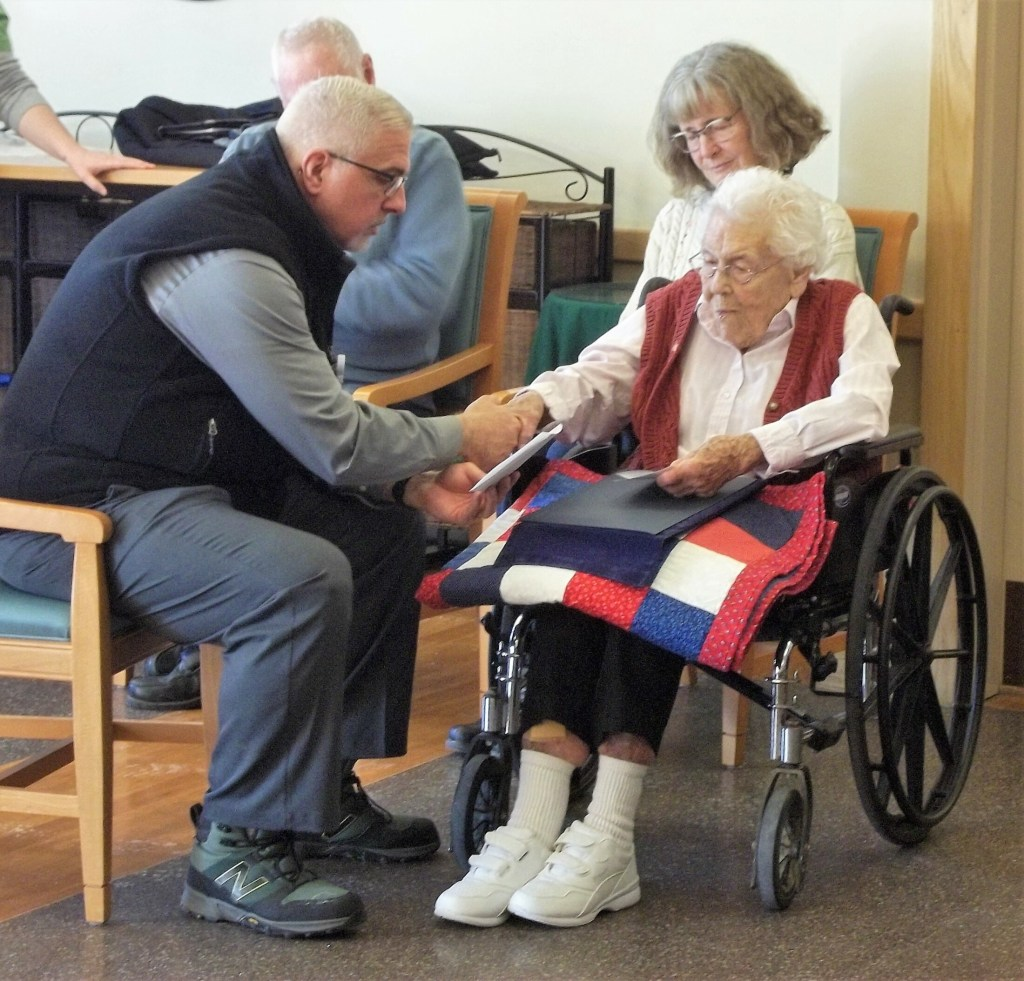 The Rev. John Bilowith, left, from Beacon Hospice, holds Jean Smith's hand while offering a small prayer on her behalf  and for all the others who have served our country, while Katie Farrin listens.