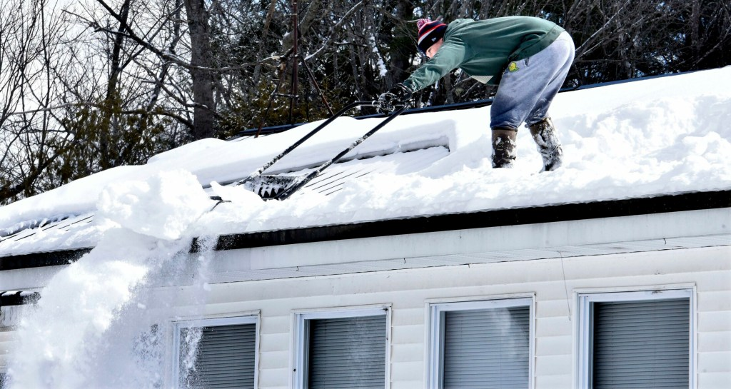 Trafton Gilbert stretches to dump snow over the slippery edge of a home in Sidney on Sunday. Gilbert was clearing the foot of snow to make room for the several inches of snow forecast to fall Monday.