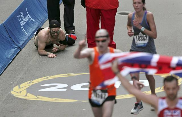 Micah Herndon crawls across the finish line at the Boston Marathon. Herndon finished the race in three hours and 38 minutes.