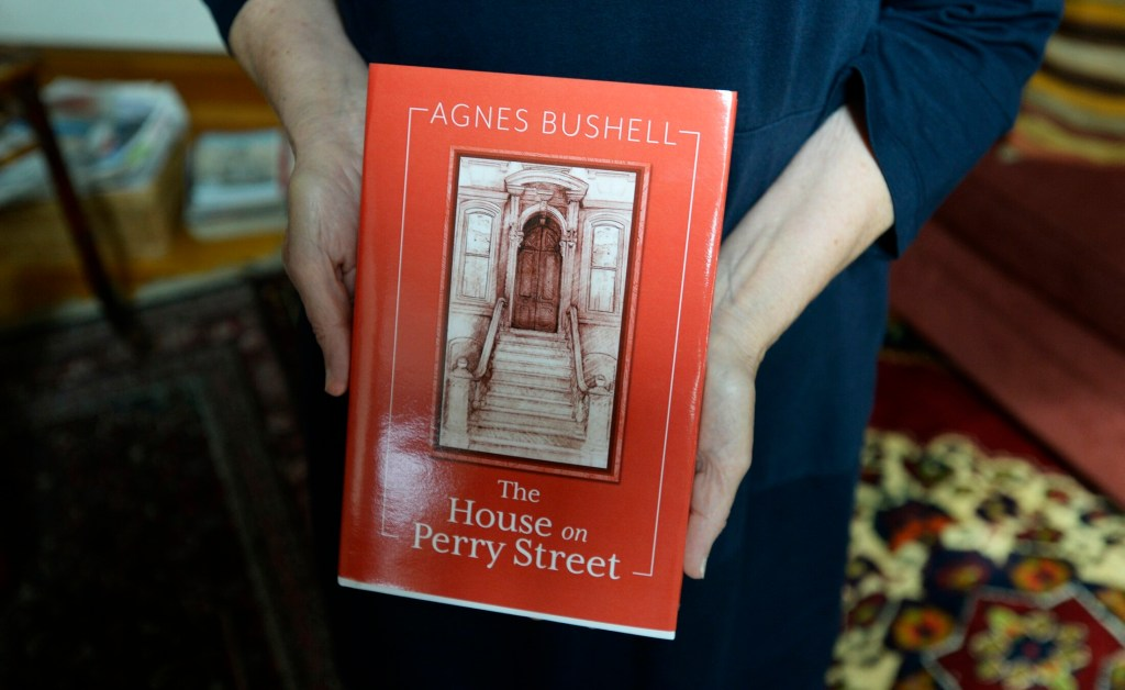 "Writer Agnes Bushell holds a copy of her book ""The House on Perry Street"" in September 2018."
