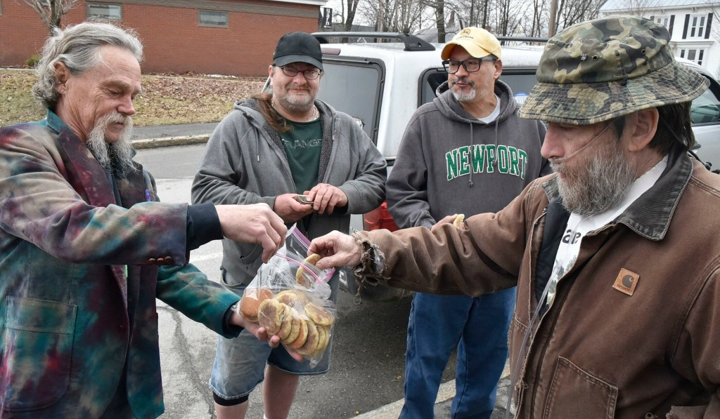 """Marijuana advocate Donny Christen, right, accepts a cookie made with pot from Robert Hardenburg, left, outside the Somerset County Courthouse in Skowhegan during the annual Patriot's Day """"smoke in"""" on Monday. Participating in the event were Joey Annaloro, second from left, and Pedro Quintela."""