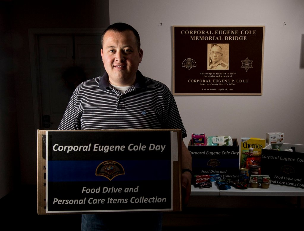Richard LaBelle, town manager of Norridgewock, stands on Friday with donations made in memory of Cpl. Eugene Cole at the Norridgewock Town Office. LaBelle said collecting food and personal items and distributing them to those in need in the community is a positive way for all to remember Cole.