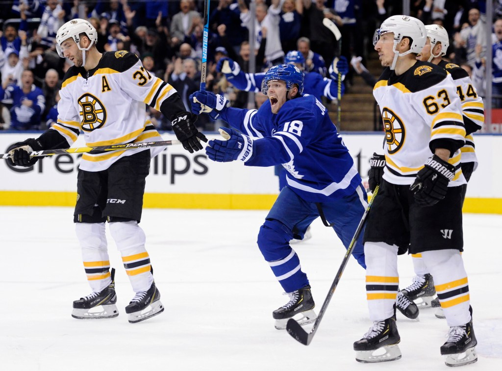 Toronto Maple Leafs left wing Andreas Johnsson (18) celebrates his goal as Boston Bruins center Patrice Bergeron (37) and left wing Brad Marchand (63) look on during second-period NHL playoff hockey action in Toronto, Monday, April 15, 2019. (Nathan Denette/The Canadian Press via AP)