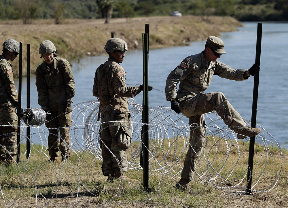 Members of the U.S. military install multiple tiers of concertina wire along the banks of the Rio Grande in Laredo, Texas at the U.S.-Mexico border in 2018.
