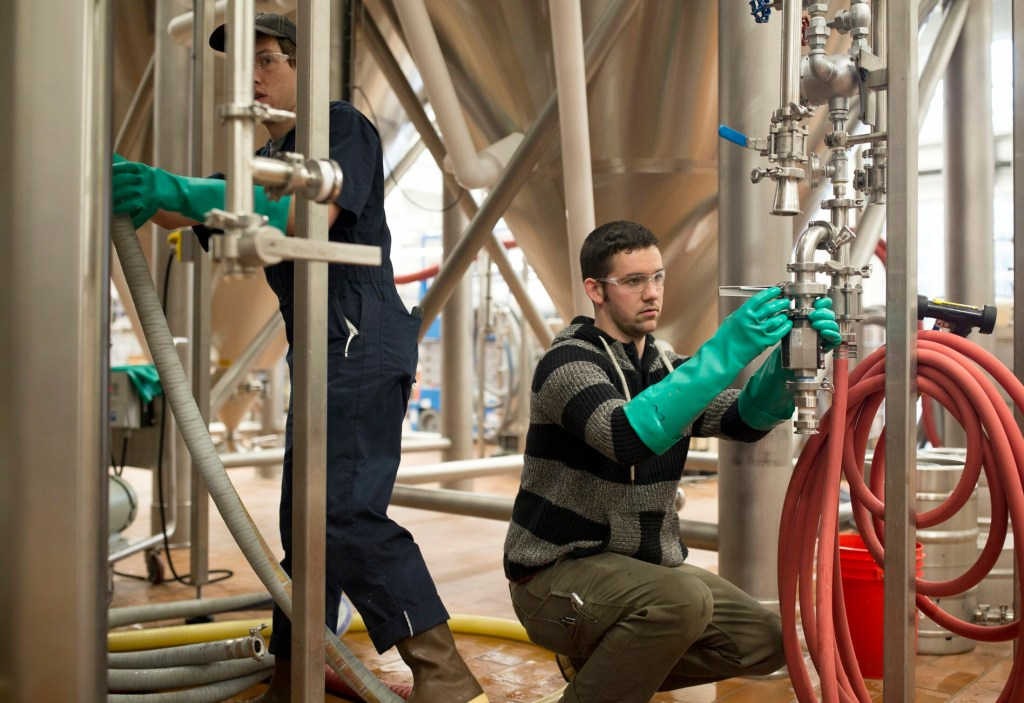 David Love, right, and Phil Neil work in the brewery at Maine Beer Co. in February. The company announced a plan Thursday to help increase renewable energy across the state.