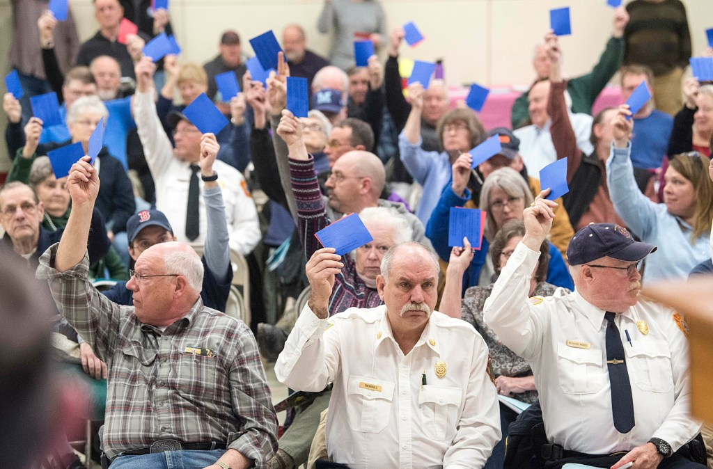 Tim Theriault, China fire chief, front row center, and Richard Morse, right, cast their votes during the annual town meeting at the China Middle School in April 2019. The fire chiefs are at loggerheads with Town Manager Dennis Heath over stipends the town pays to the volunteer departments.