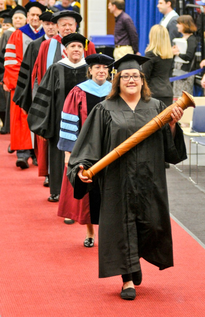 Jacquelyn Estrella carries the mace and leads the procession Saturday at the beginning of the University of Maine at Augusta commencement at the Augusta Civic Center.