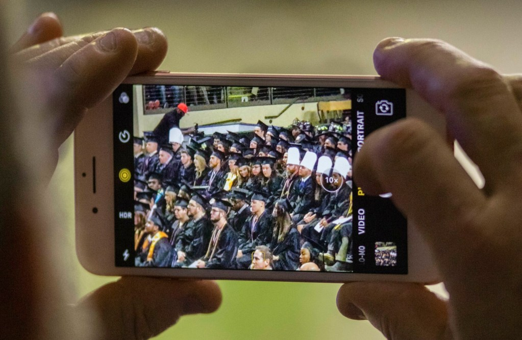 PORTLAND, ME - MAY 12:  An attendant at the Southern Maine Community College commencement, at Cross Insurance Arena in Portland, enlarges a phone photo to get a better look at the graduate they were there to support on Sunday, May 12, 2019.(Staff Photo by Carl D. Walsh/Staff Photographer)