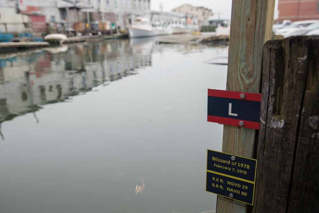 "A plaque shows the low-end estimate for water level in 2050 on Portland Pier in the event of a storm like the ""Blizzard of 1978."" Sea-level resilience strategies are on Maine's to-do list."