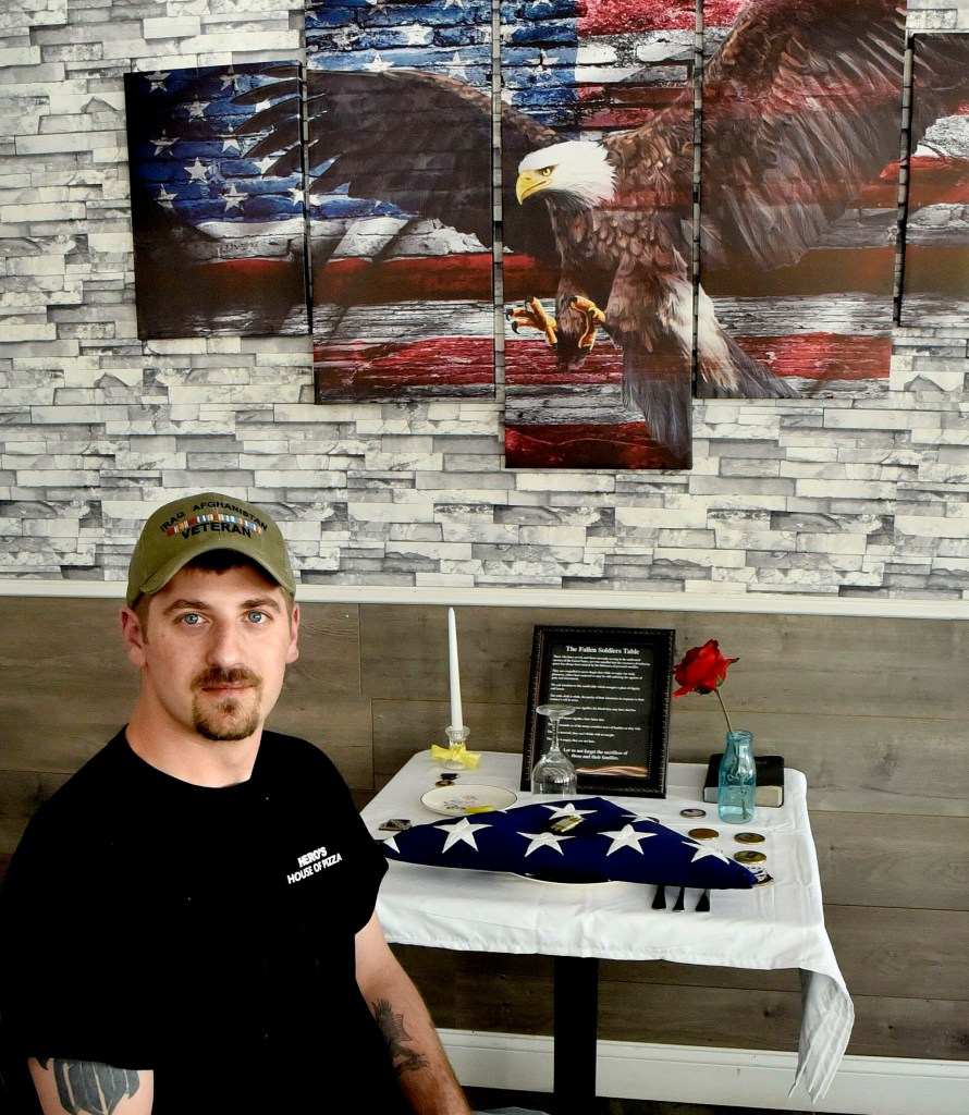 Veteran Derek DeFelice sits on Wednesday at the Fallen Soldiers Table at his Hero's House of Pizza in Skowhegan. DeFelice, who will be the grand marshal of the Skowhegan Memorial Day parade this Monday, created the table in honor of veterans who died fighting in wars.