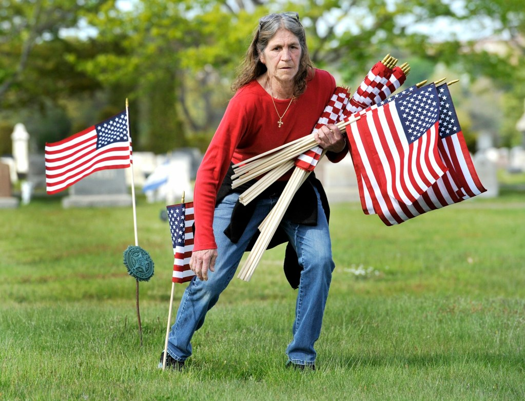 Paula Hollenkamp places American flags on veterans' graves at the Forest City Cemetery in South Portland on Wednesday.