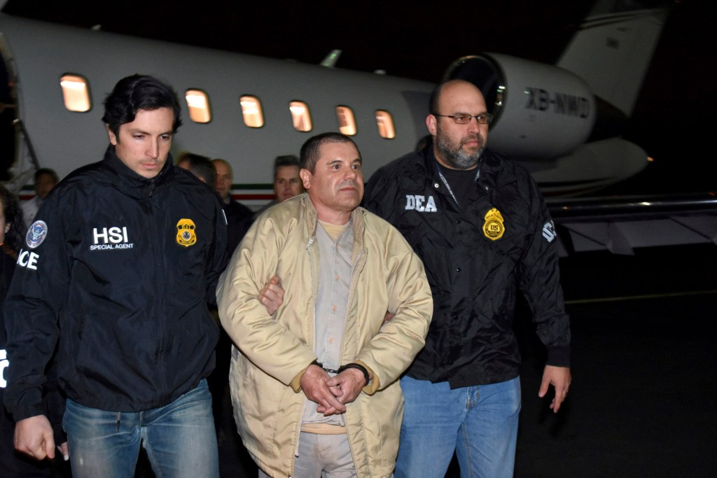 """In this Jan. 19, 2017 file photo provided U.S. law enforcement, authorities escort Joaquin """"El Chapo"""" Guzman, center, from a plane to a waiting caravan of SUVs at Long Island MacArthur Airport, in Ronkonkoma, N.Y."""
